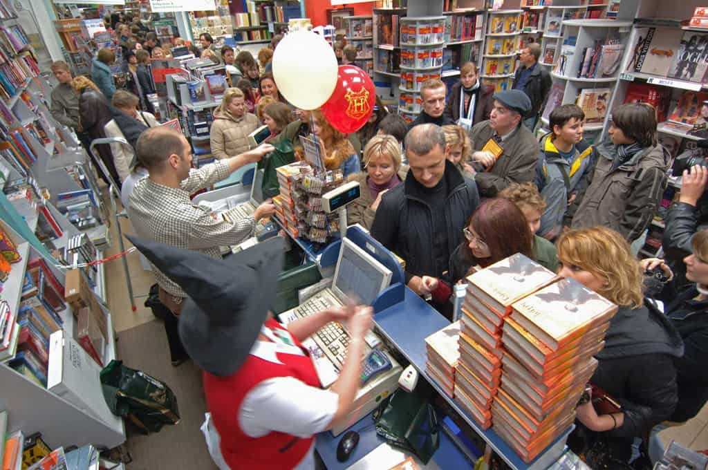 shows people lined up in a book store waiting to buy the lastest book in the Harry Potter series