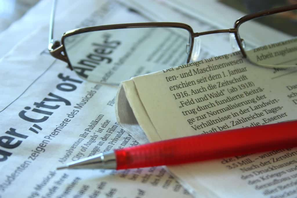 pen an glasses sitting on top of a newspaper article